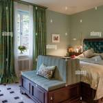 Aquamarin Samt Zugeknopft Kopfteil Auf Bett Im Schlafzimmer Mit Grun Und Gold Print Vorhange Stockfotografie Alamy