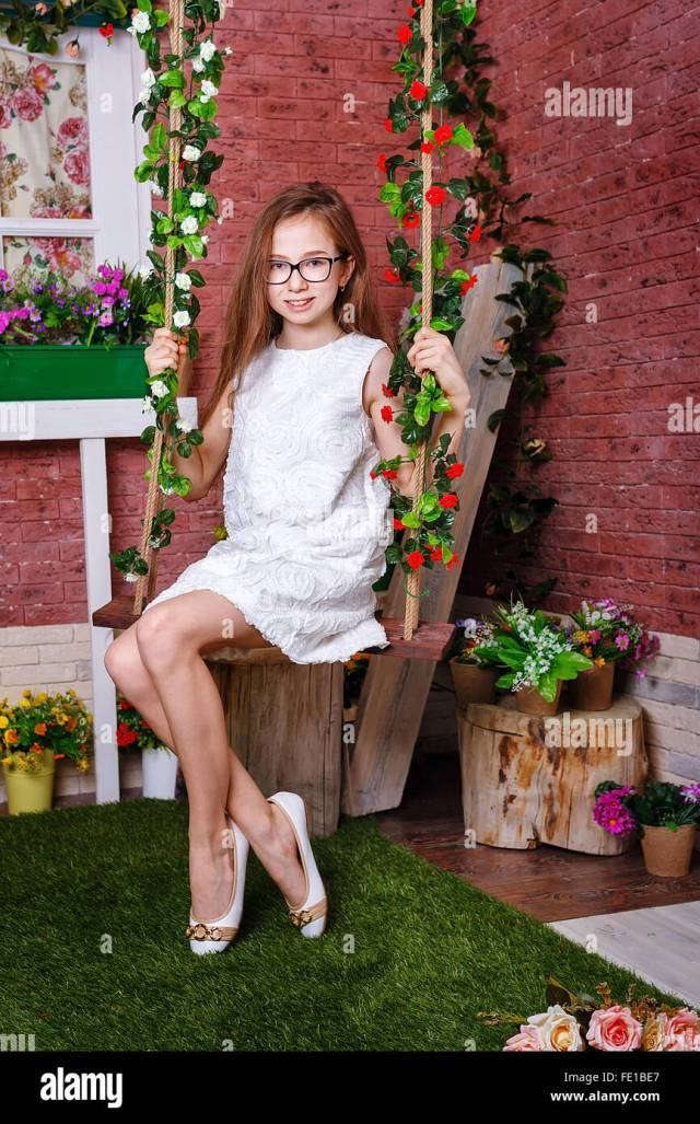 Cute Teenies Madchen In Glasern Sitzt Auf Einer Schaukel Schaukel Mit Blumen Geschmuckt