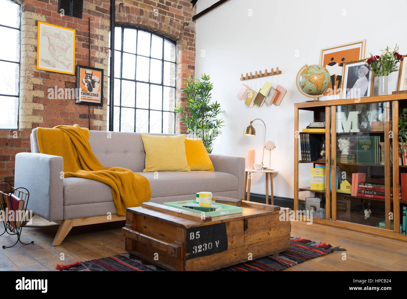 Ein Wohnzimmer mit Backsteinwnden und eine graue Danish Design Sofa mit gelben Decke und Kissen