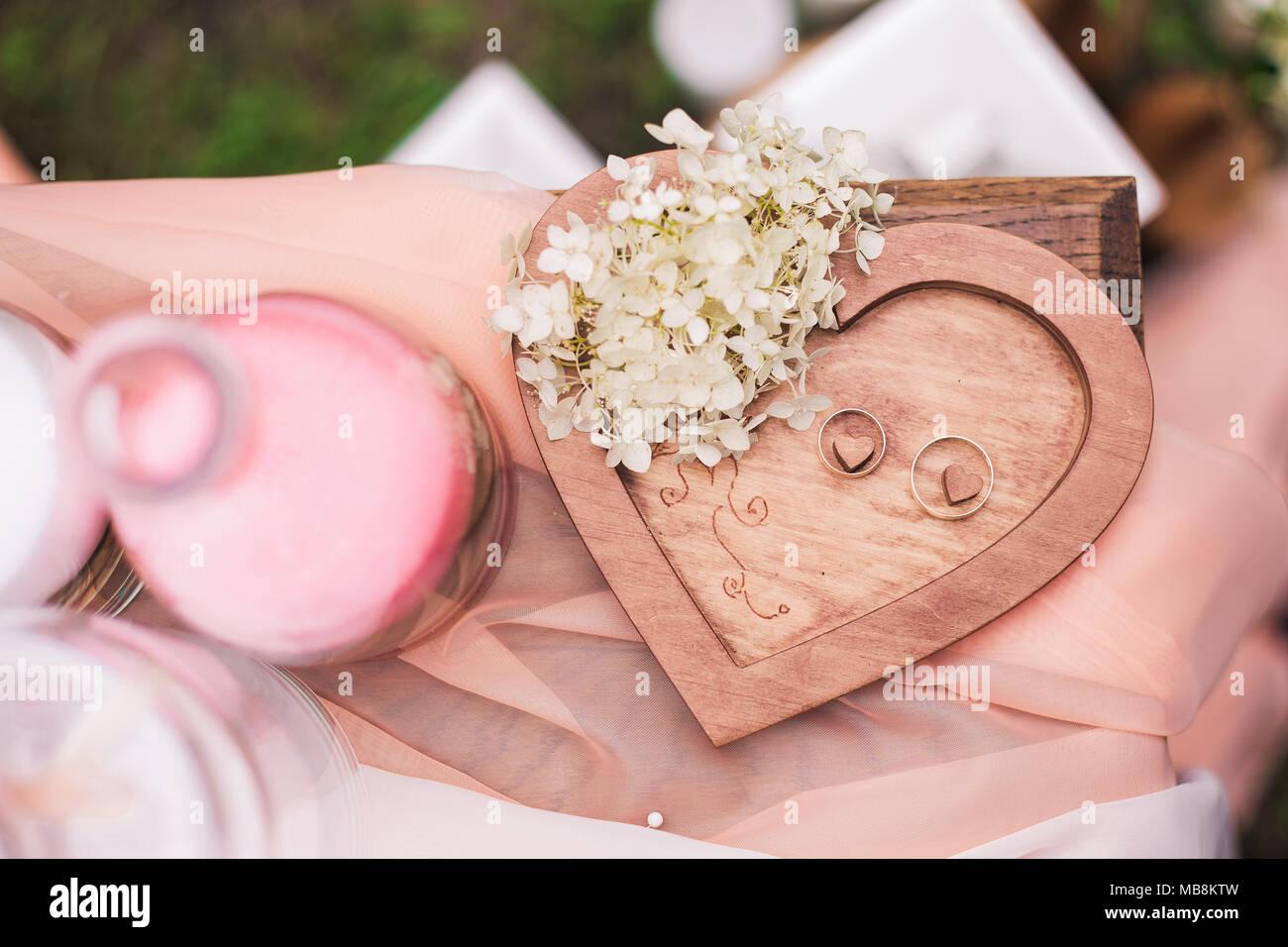 Nahaufnahme Blick von oben auf die beiden goldenen Hochzeit Ringe auf Holz Herz Hintergrund mit