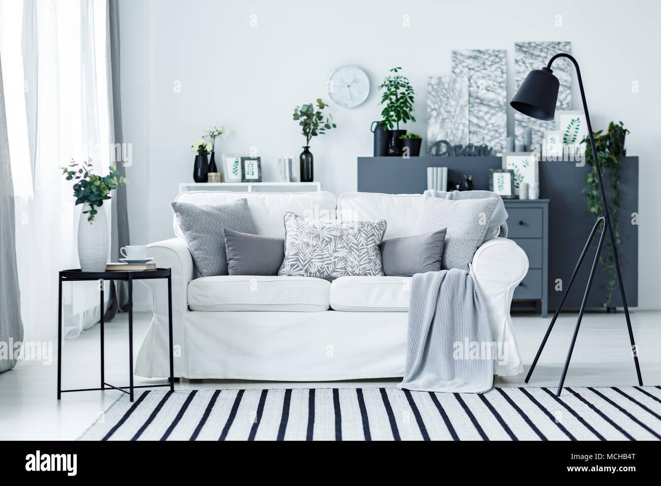 Grau Wei Sofa mit Kissen und Decke im hellen Wohnzimmer Interieur mit Metall Lampe Frische
