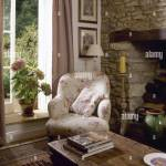 Landhaus Wohnzimmer Detail Mit Einem Offenen Fenster Holz Tisch Einen Geblumten Gepolstertem Sessel Neben Einem Stein Kaminecke Stockfotografie Alamy