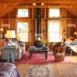 Gepolstertes Sofa Gegenuber Stuhle Aus Holz Im Landhausstil Wohnzimmer Mit Holzwanden Stockfotografie Alamy