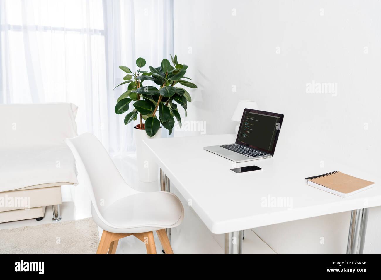 laptop mit html code smartphone und notebook auf dem tisch im wohnzimmer