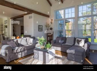 Vista interior de la sala de estar con sofás de color gris oscuro alfombra y pisos de madera de roble teñidos dentro de la casa de estilo rural Quebec Canadá Fotografía de