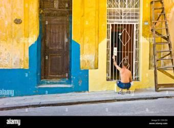 Un hombre es pintar el exterior de su casa en La Habana Brillantes colores azul amarillo y rosa son predominantes Fotografía de stock Alamy