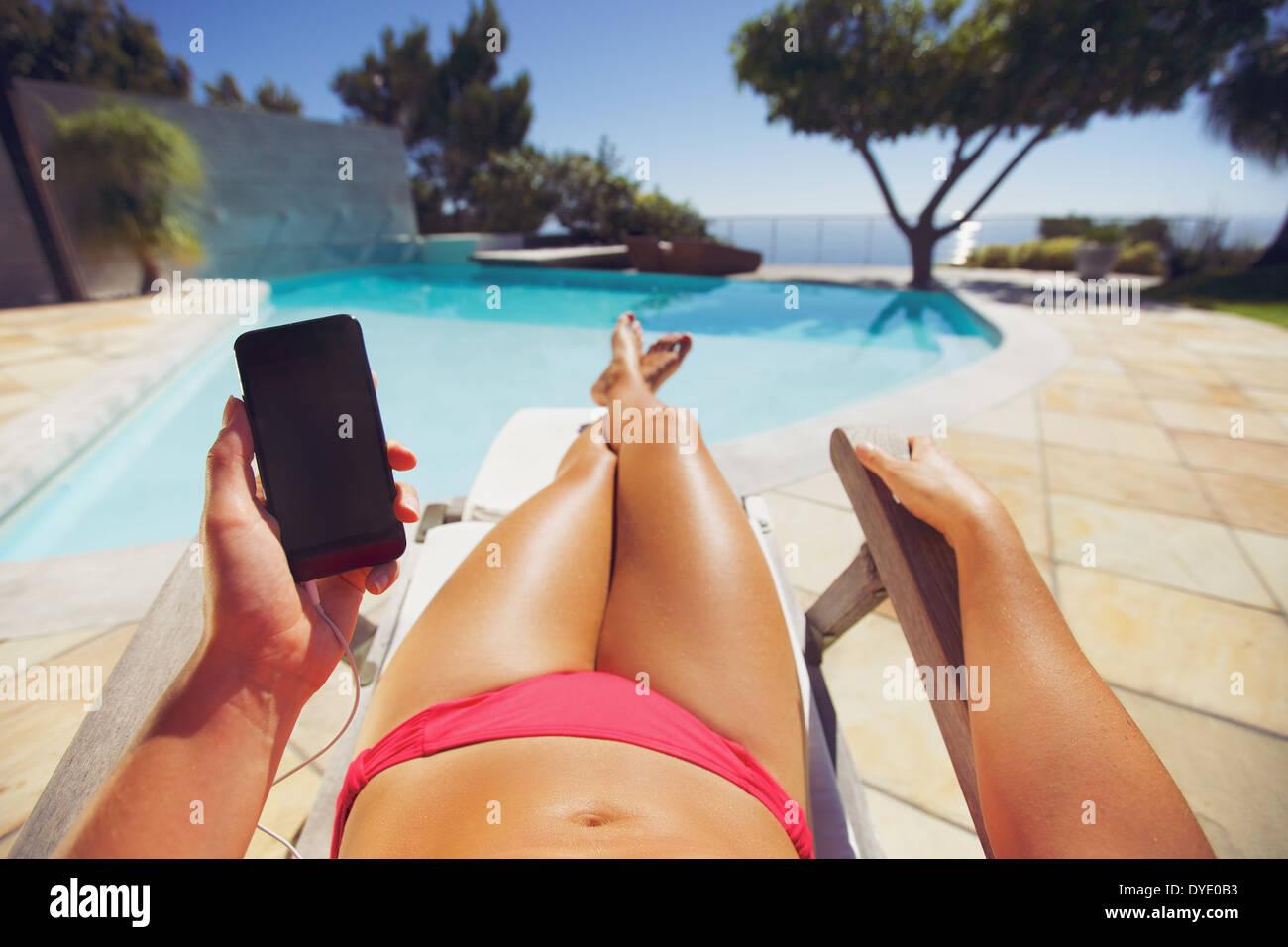 Seorita vistiendo bikini a travs de telfono mvil mientras toma el sol en la piscina Modelo