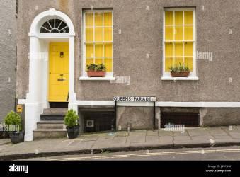 Exterior de casa tradicional británico en Queens Parade Bristol Reino Unido Con paredes de color gris amarillo puerta frontal y dos ventanas con cortinas amarillas Flores Fotografía de stock Alamy