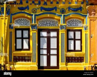 Tradicional Singapur tienda exterior con fachada amarilla ventana en arco y persianas de madera en el histórico Little India District Fotografía de stock Alamy