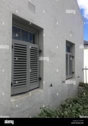 Vista frontal de la casa gris pálido con la mitad de persianas cerradas que son de