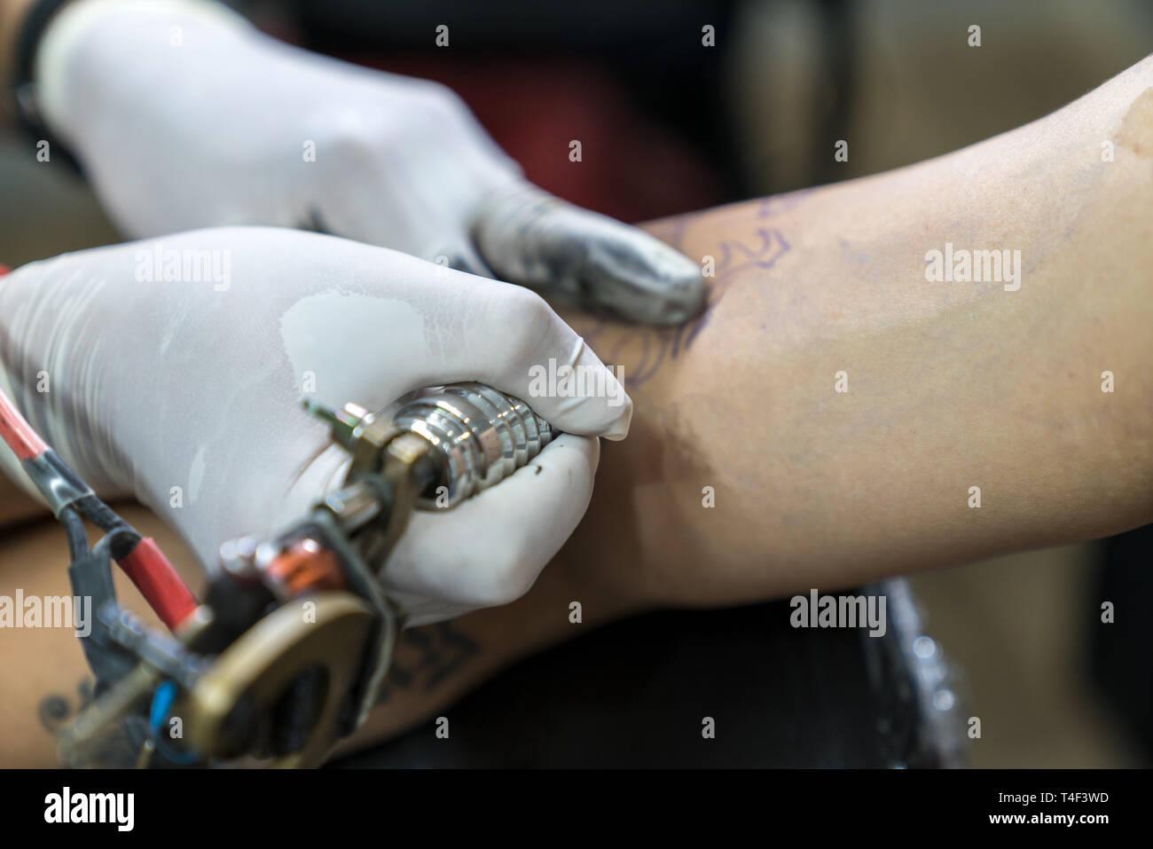 Tatuajes De Guantes Blancos Haciendo Un Tatuaje En El Brazo De