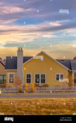 El exterior de una casa de un solo piso con paredes de color amarillo y gris