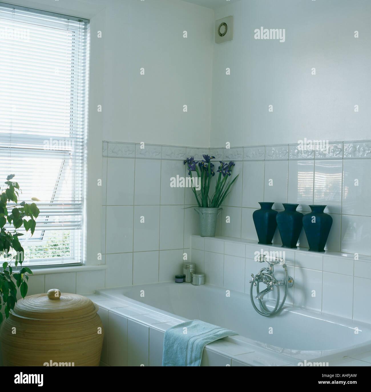 https www alamyimages fr photo image rangee de casiers sur sol carrele etagere au dessus de baignoire en blanc salle de bains avec murs carreles a hauteur de dado 14460000 html