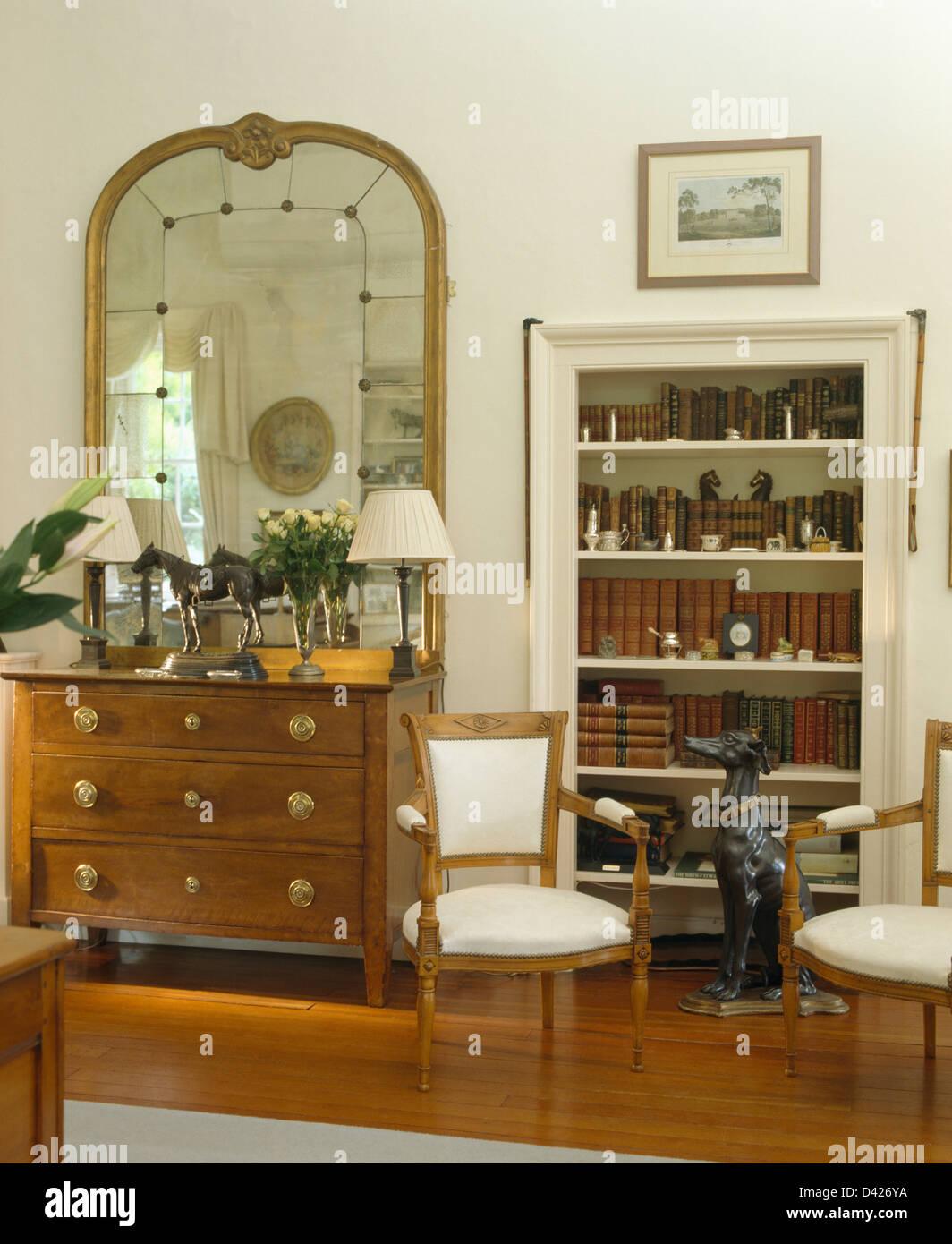 grand miroir au dessus de commode en pays sejour avec alcove et d etageres de haut statue de chien assis