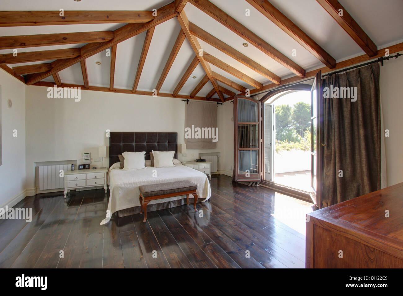 Les draps blancs sur lit rembourr en espagnol avec poutres apparentes chambre avec du parquet