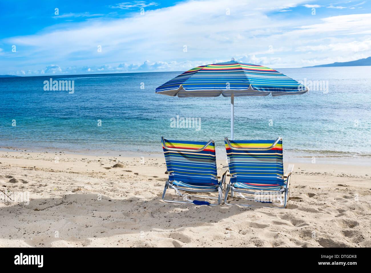 https www alamyimages fr deux chaises de plage avec parasol sur le bord de l eau d une plage tropicale image66744812 html