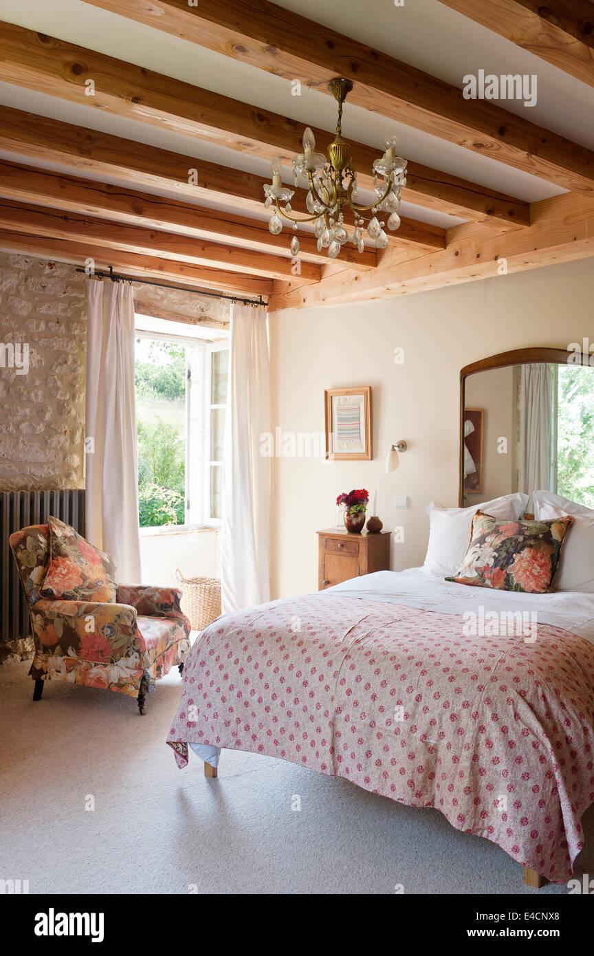 persan antique quilt brode sur le lit dans la chambre avec des murs en pierre et des poutres apparentes le fauteuil est recouvert de fl