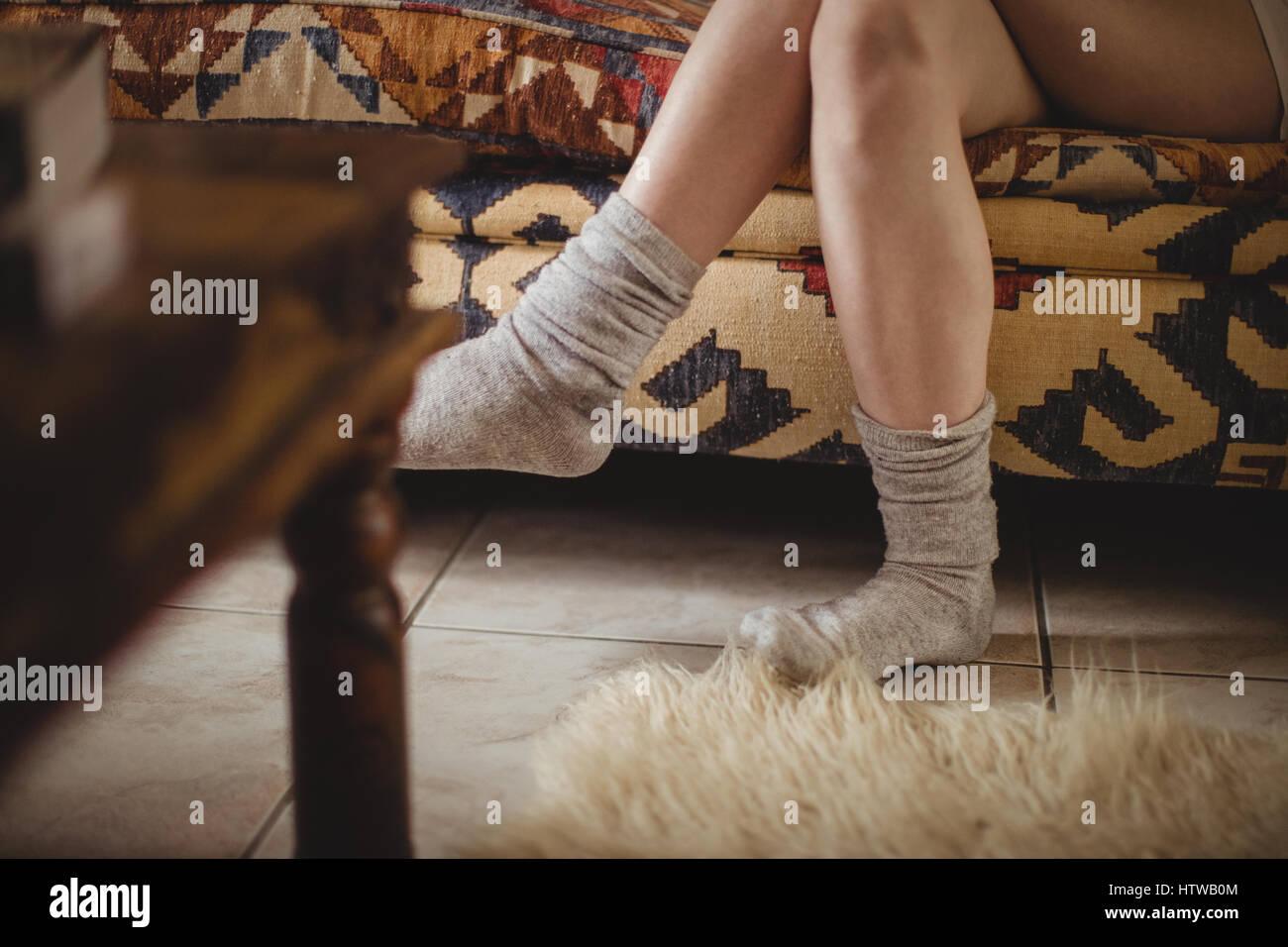 chaussettes femme portant assis sur un canape avec les jambes croisees