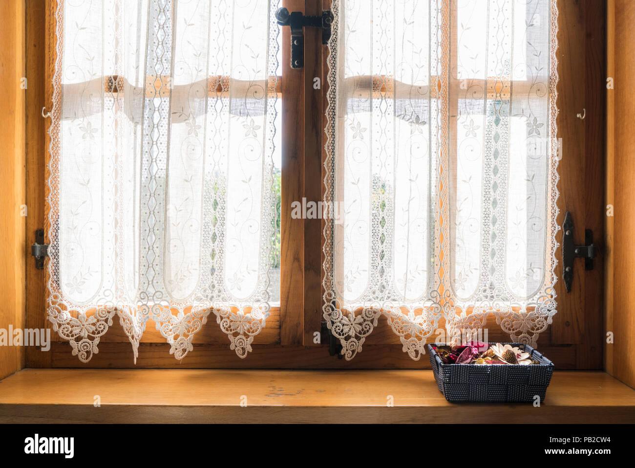 https www alamyimages fr une fenetre en bois avec un rideau brode blanc et un petit panier de fleurs sechees sur le rebord image213339648 html