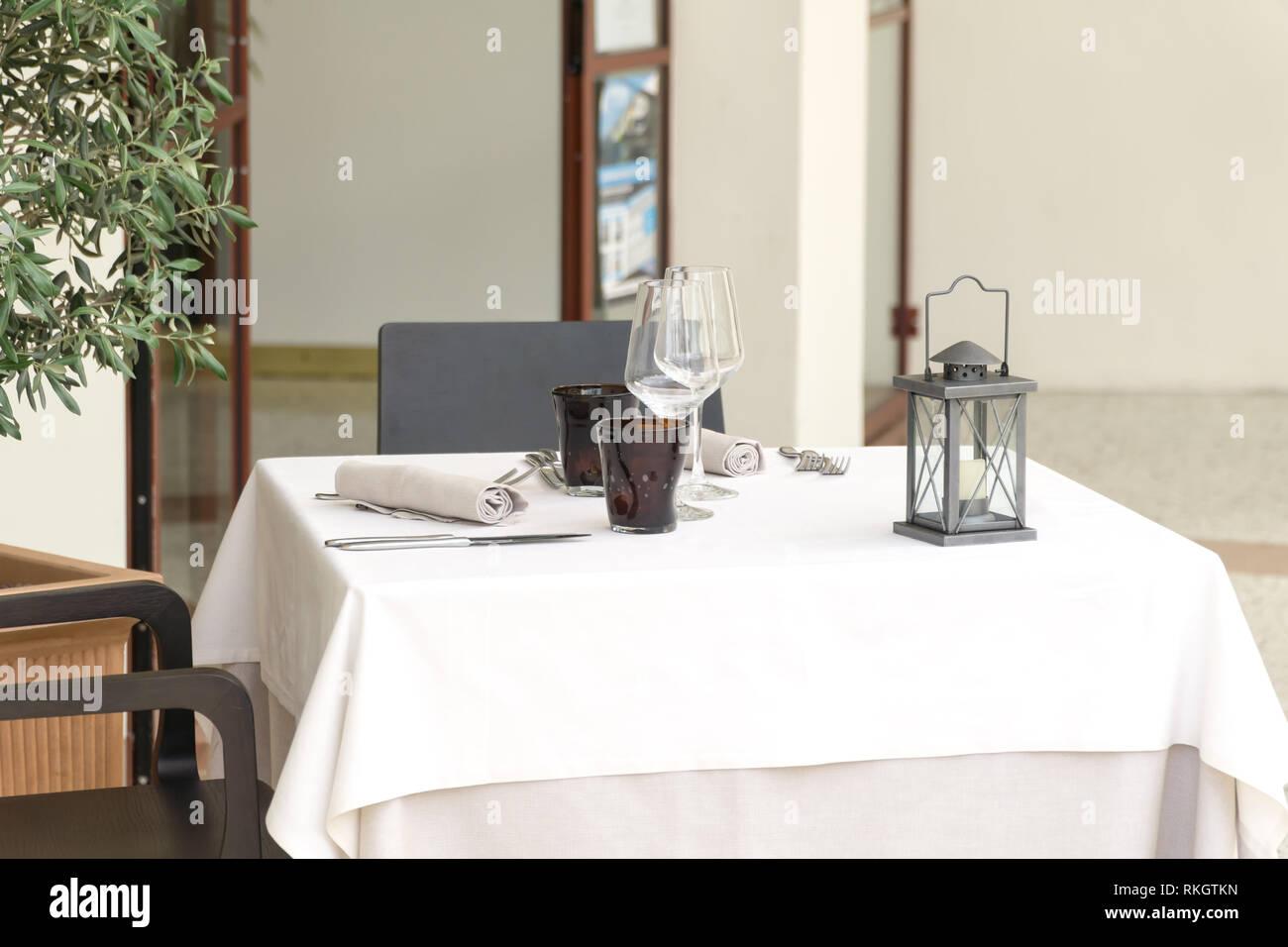 https www alamyimages fr une table vide pour deux dans un restaurant recouverte d une nappe blanche avec deux sets de table et d une lanterne dans un cafe ou un restaurant a l exterieur image235783849 html