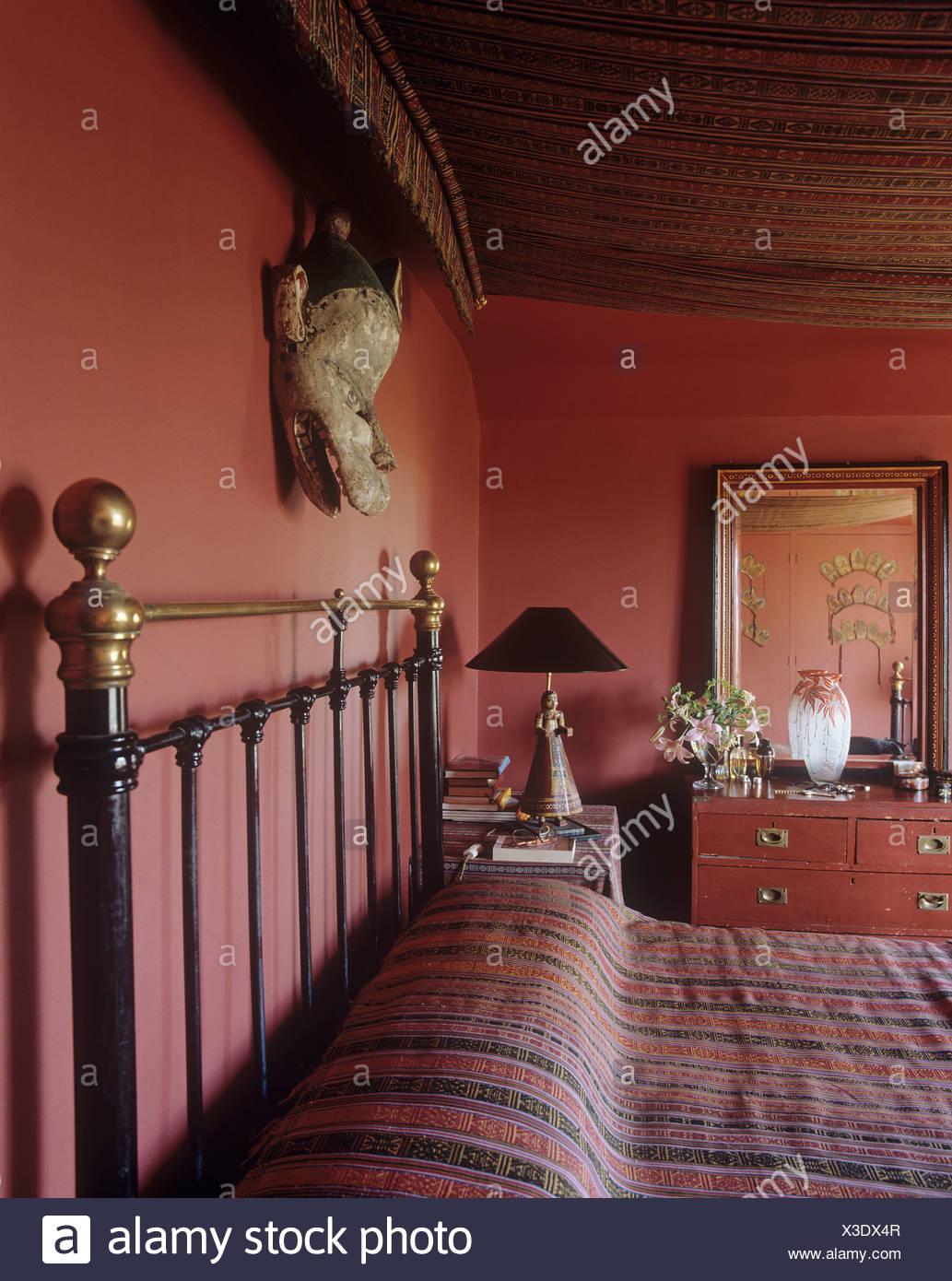 https www alamyimages fr masque sur le mur au dessus de lit en cuivre avec couvercle a rayures et tissu canopy en chambre rouge fonce image277515751 html