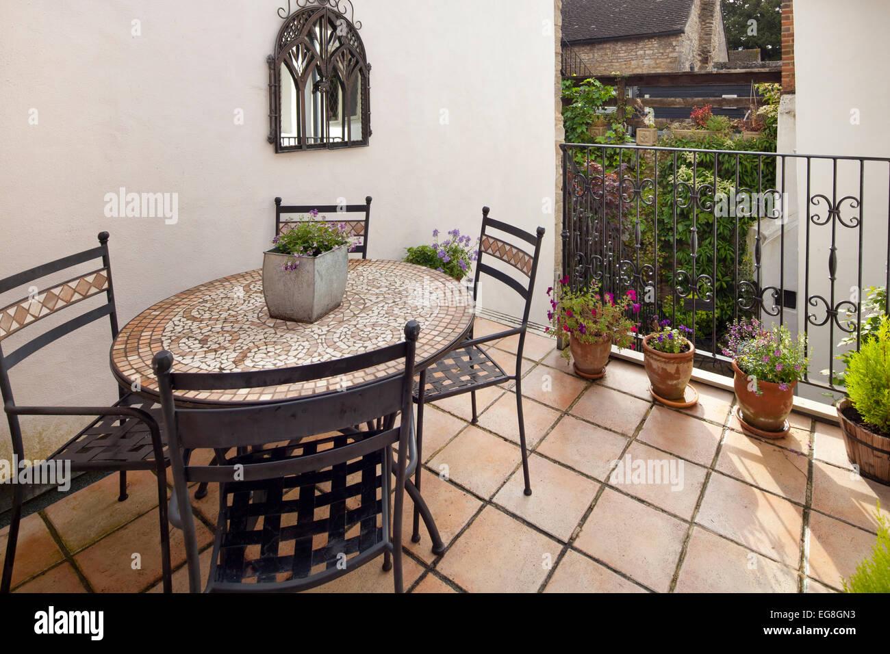 Piccolo balcone con pavimento in piastrelle di terracottapot esterno e posti a sedere di