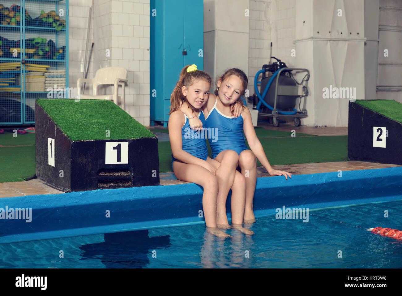 Due sorridenti ragazze della scuola seduti in piscina Foto  Immagine Stock 169560308  Alamy