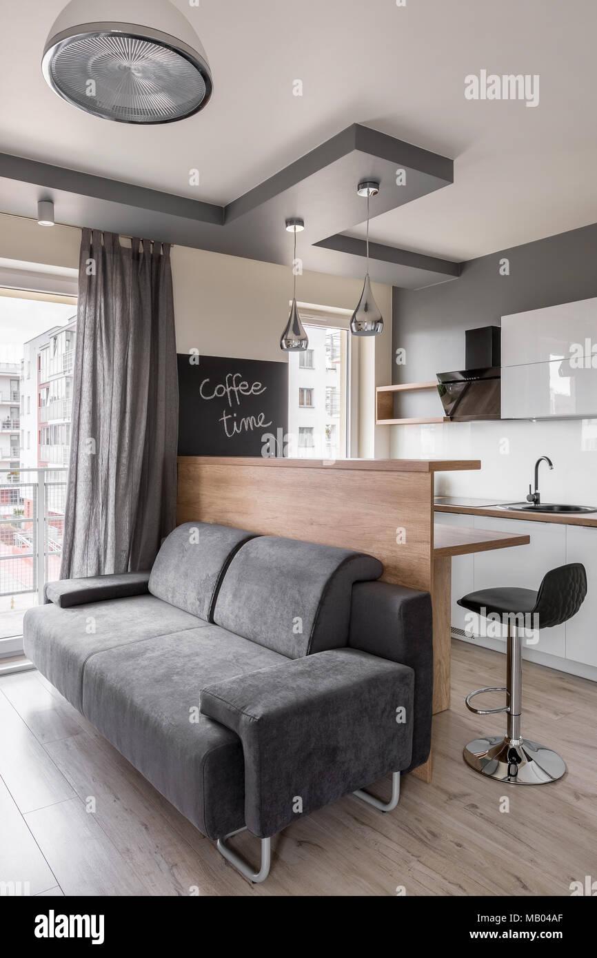 Soggiorno con divano grigio e nero sgabello da cucina Foto