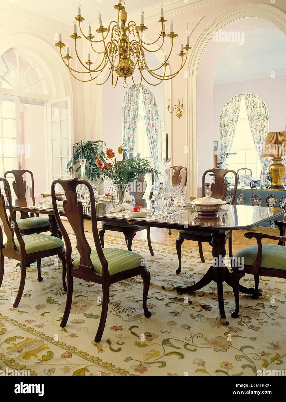 Un lampadario della sala da pranzo (o un altro apparecchio appeso al soffitto) è tradizionalmente appeso sopra il centro del tavolo da pranzo ed è un elemento di design primario nella stanza. Lampadario Su Tavolo Da Pranzo In Legno E Sedie In Lussuosa Camera Foto Stock Alamy
