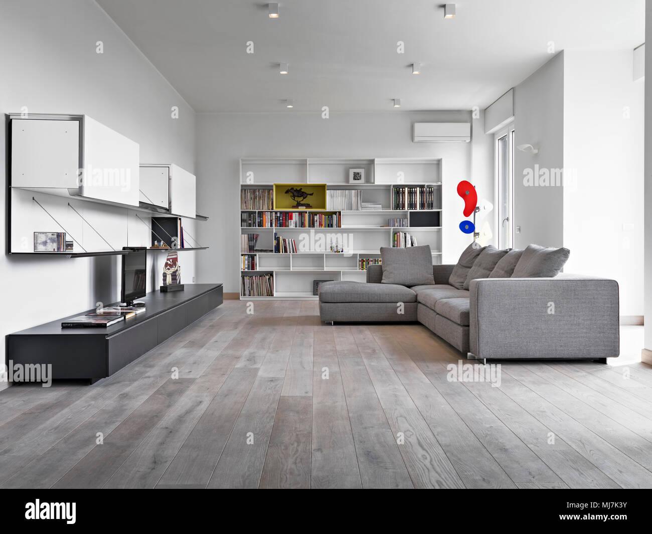 Scatti di interni di un soggiorno moderno con tessuto grigio divano e pavimento in legno Foto
