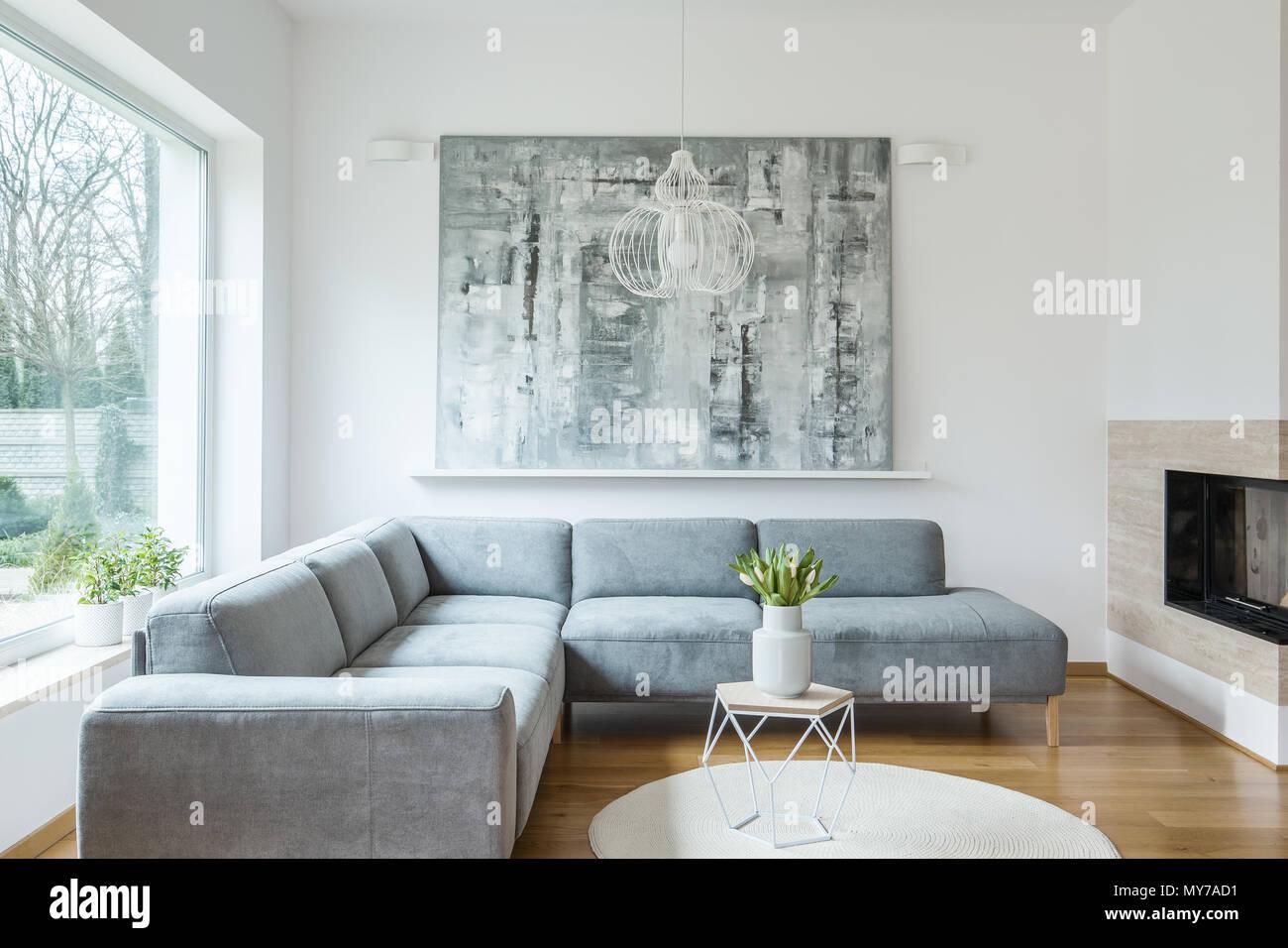 Grigio Divano Ad Angolo Contro Il Muro Bianco Con Pittura In 37008e73bd67