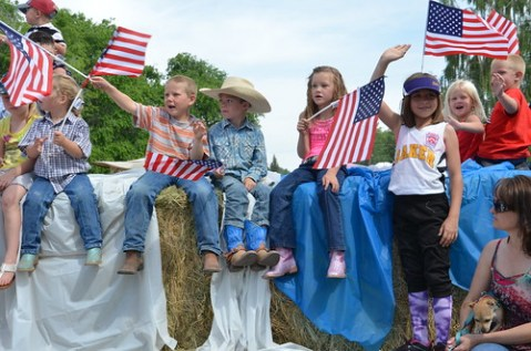 Kids on 4th of July parade with flags
