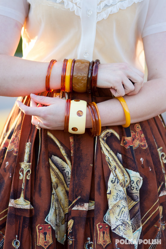 The warm brown tones of this 1950s music-themed novelty print skirt are a perfect match for a selection of Bakelite bangles