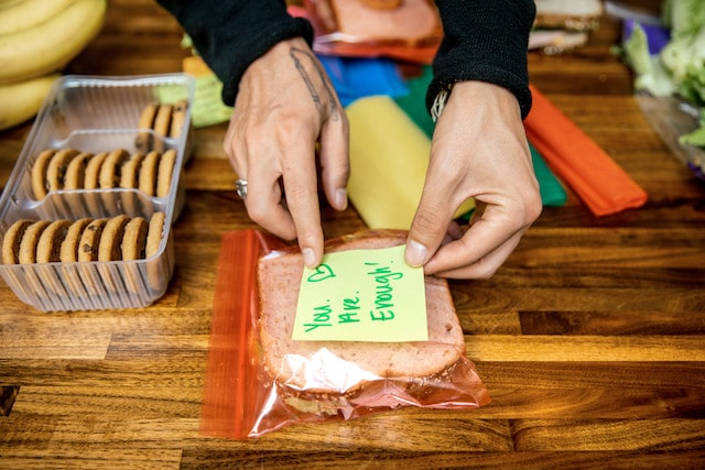 Person making sandwiches and adding sticky note messages to the bags