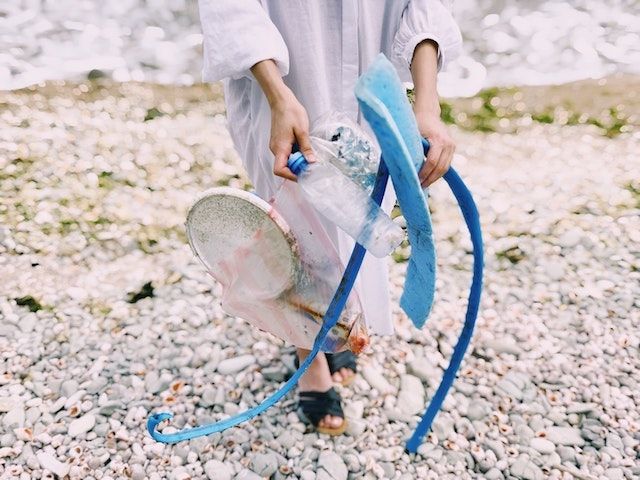 Person on a beach carrying plastic bottle and other trash