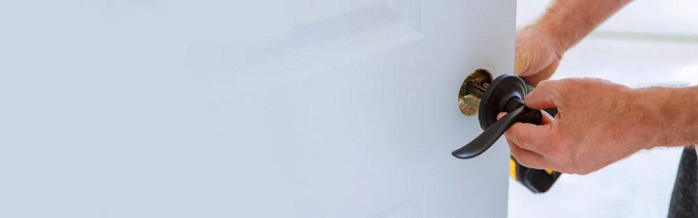 medium resolution of man installing a door lock on a white door
