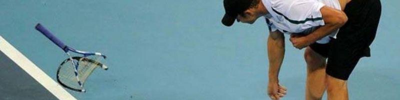 player smashes tennis racket