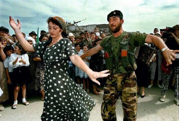 A Chechen woman dances with a rebel fighter in the centre of Grozny September 6, celebrating the fif..