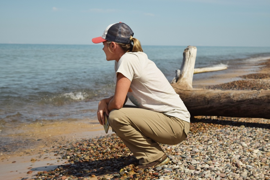 outdoor adventure t-shirts: woman squatting near a lakeshore wearing a tan t-shirt and blue cap