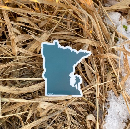 Women Hike MN sticker in fall grass with snow