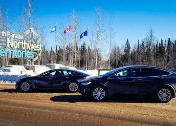 Two Tesla electric vehicles sit next to the sign welcoming visitors to the Northwest Territories - James Locke