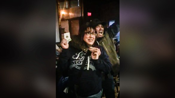 A woman identified as Adeline Football, from Wekweeti, holds the Ace of Spades at the Monkey Tree Pub on April 20, 2018