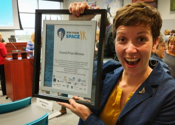 Mary Kelly, creator of music space, holds her grand prize-winning certificate at City Hall after winning Yellowknife's Win Your Space 2018