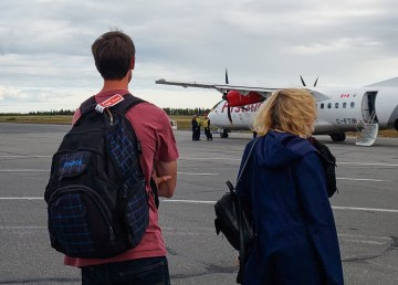 Passengers wait outside an aircraft operated by First Air following an order to evacuate the cabin on August 30, 2018
