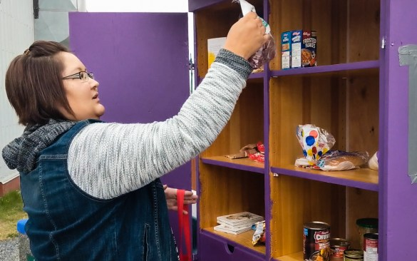 Renee Sanderson stocks a pop-up pantry in Yellowknife's pop-up park