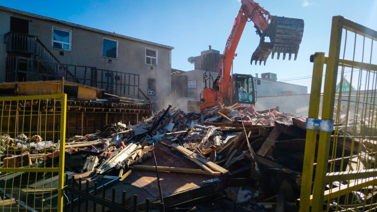 A worker clears rubble following the demolition of Yellowknife's Fat Fox building in September 2018