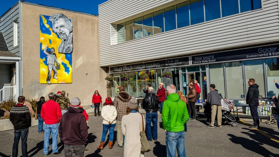 Gail Cyr addresses residents beneath a mural dedicated to Charlie Delorme