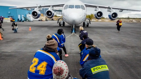 RCMP officers pull an aircraft to raise money for Special Olympics NWT in September 2018