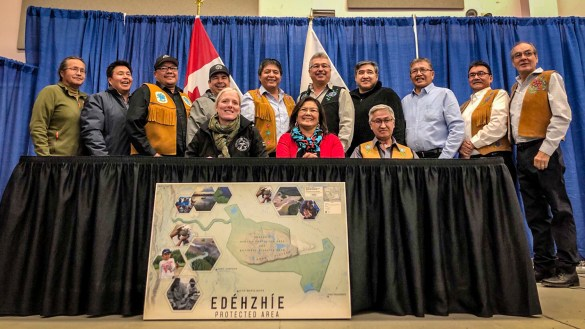 Catherine McKenna, front left, and Gladys Norwegian, front centre, pose on signing the Edehzhie Establishment Agreement in October 2018