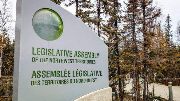 A file photo of a sign standing at the entrance to the NWT's Legislative Assembly in Yellowknife